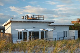 A small beach retreat originally dating from the 1950s on Fire Island, New York, was revamped by interior designer Alexandra Angle. With a location high on a hill overlooking the water, an outdoor roof terrace and patio help bring the outdoors in.