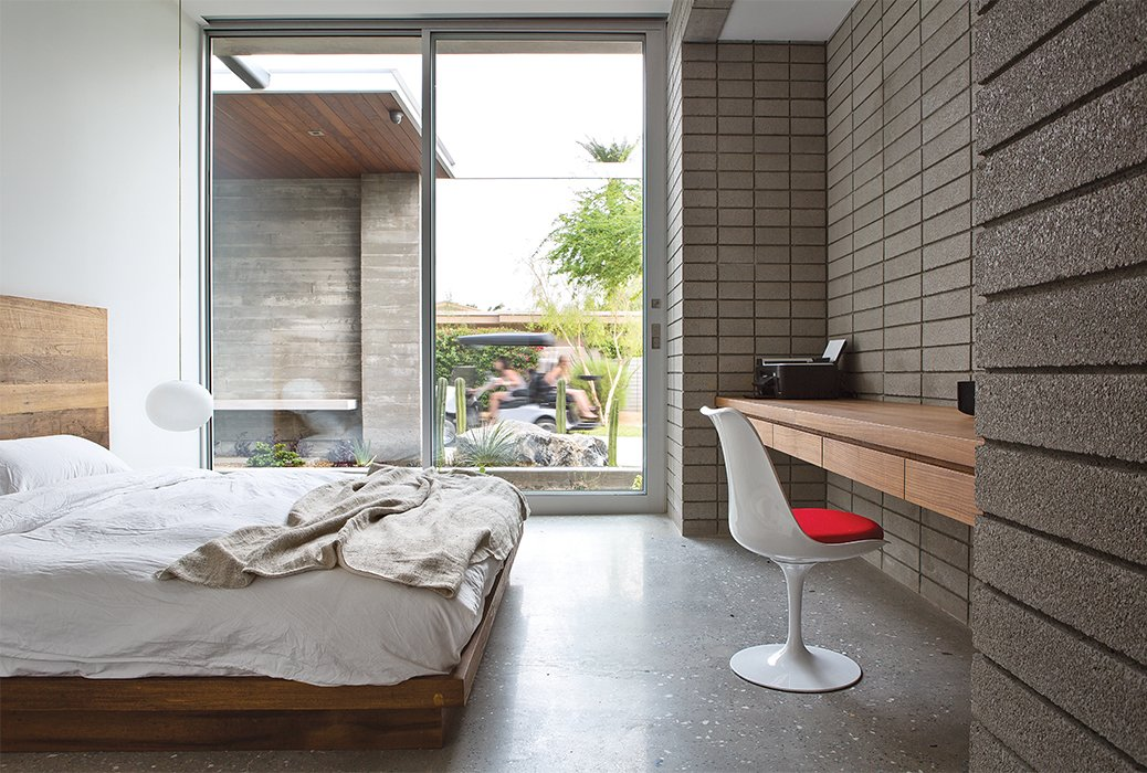 Bedroom, Shelves, Bed, Concrete Floor, Pendant Lighting, and Chair A Glo-Ball pendant from Flos and a Saarinen chair brighten a guest bedroom. The teak headboard is from Central Station.  Bedrooms by Dwell from Vacation Home in the California Desert is a Modernist Oasis