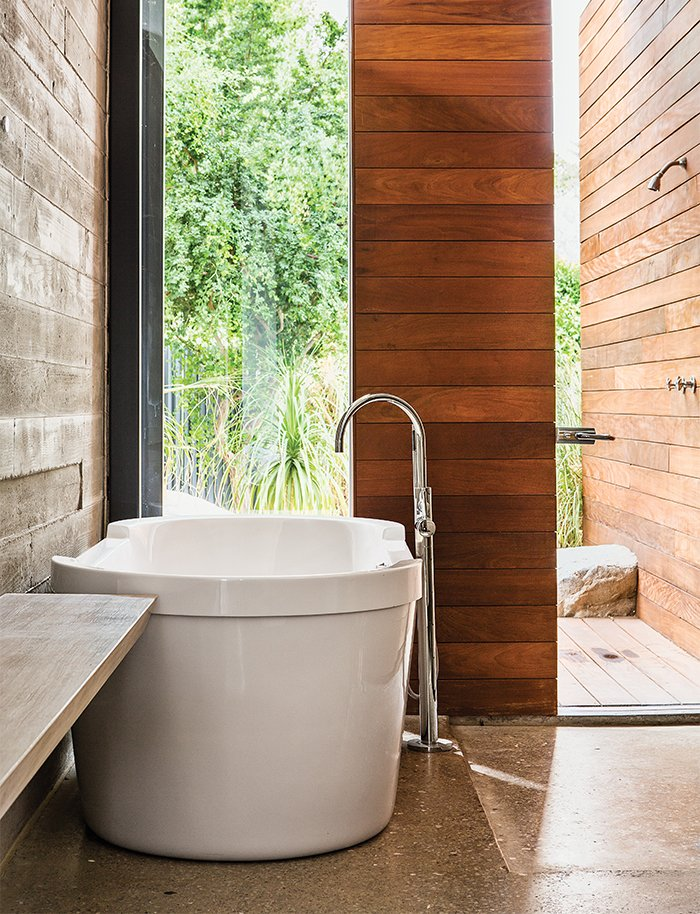 Bath Room, Wood Counter, Concrete Floor, Freestanding Tub, and Soaking Tub A family's getaway in the California desert includes a spa-like main bath with a large soaking tub that connects to an outdoor shower.   Dwell's Favorite Photos from Vacation Home in the California Desert is a Modernist Oasis