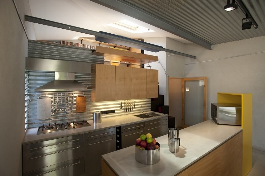 Hewing to budget constraints, Langston-Jones utilized IKEA cabinetry. The kitchen counter is fashioned from cement sheets burnished in the same sealer as the floor, providing textural continuity. The island's yellow edge is made from painted MDF.  Photo 3 of 10 in Compact Australian Home Clad in Steel and Concrete