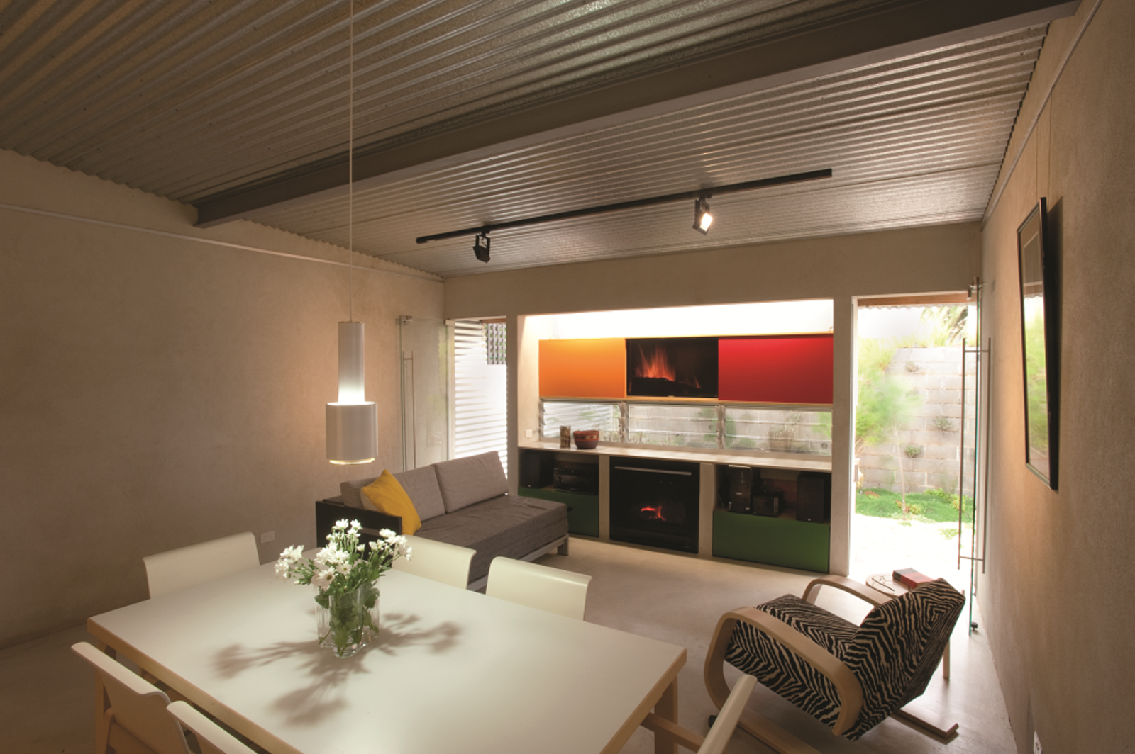 The Alvar Aalto dining chairs, which sit against a table (Table 86A) and lamp (Pendant Lamp A110) by the same designer, were deliberately chosen because they sit slightly lower to the ground and can be used in the living area as well. The back wall unit includes a television, garden-view windows, and fireplace, surrounded by an Aalto chair (Armchair 400) and a daybed from a Melbourne designer. The window's placement allows residents to look out on the garden while blocking the views from the neighboring eight-story apartment building.  Photo 4 of 10 in Compact Australian Home Clad in Steel and Concrete