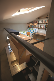 The lofted room is adorned with inexpensive features, such as a wall of Spur shelving with aluminum brackets.