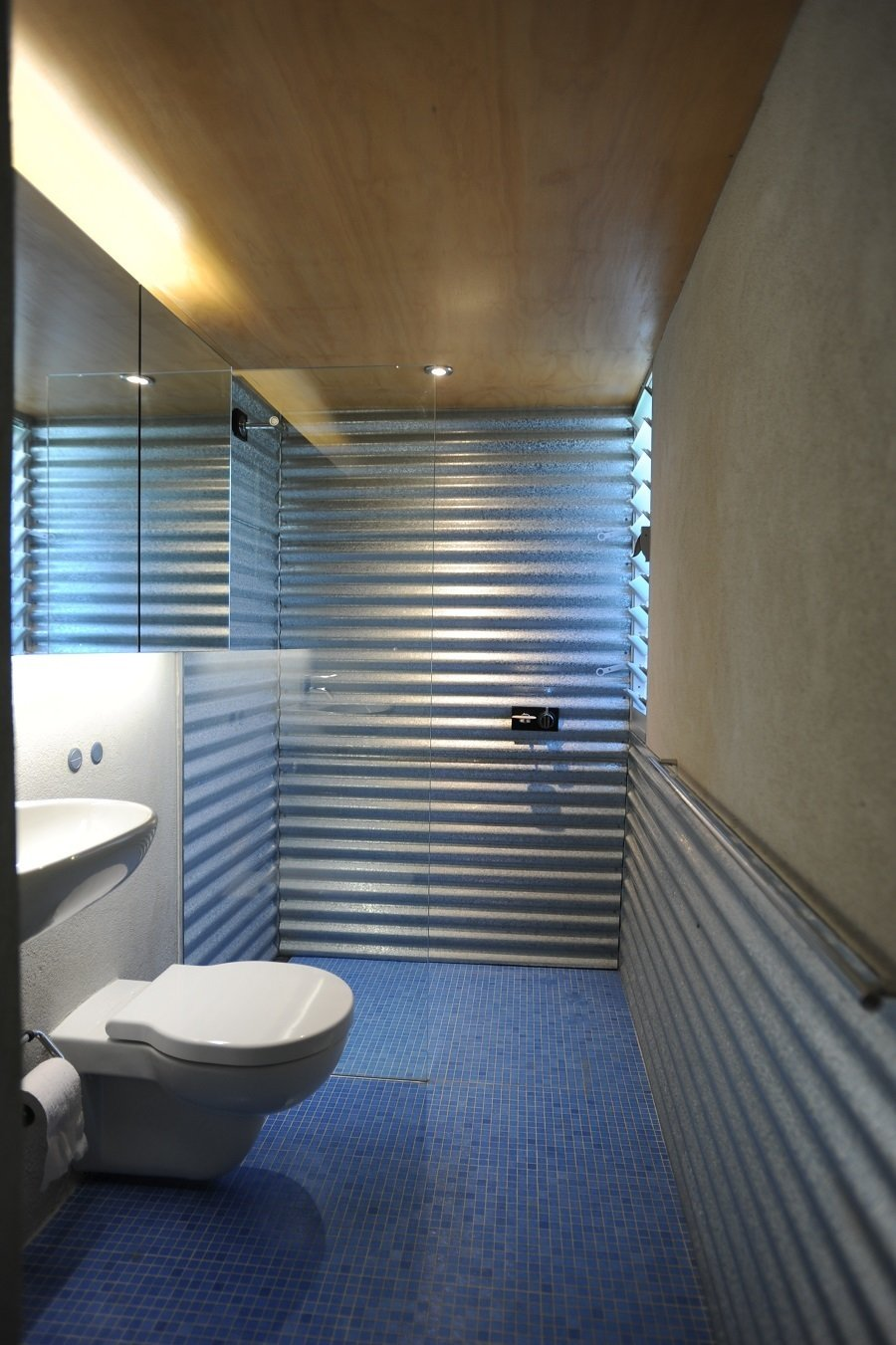 """The blue bathroom tiles were inspired by a """"Corbusian use of color,"""" according to the architect, and take advantage of the lowered floor to create a metaphorical step into a pool. The corrugated metal continues throughout, even wrapping around the walls of the shower.  Renovations from Compact Australian Home Clad in Steel and Concrete"""