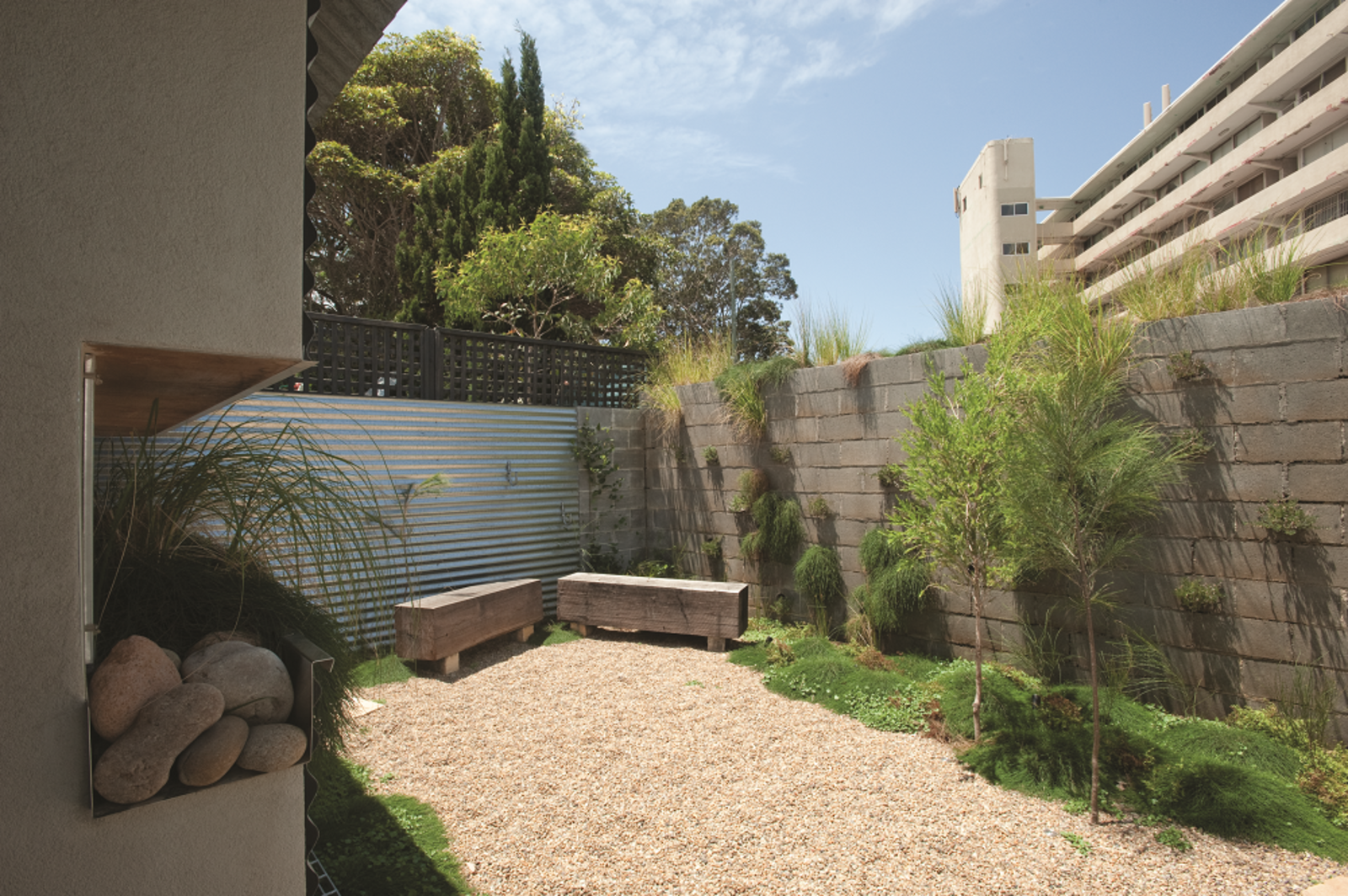 The back wall of the garden, made from stacked concrete blocks, was initially meant to be a row of vertical planting boxes.  Photo 9 of 10 in Compact Australian Home Clad in Steel and Concrete