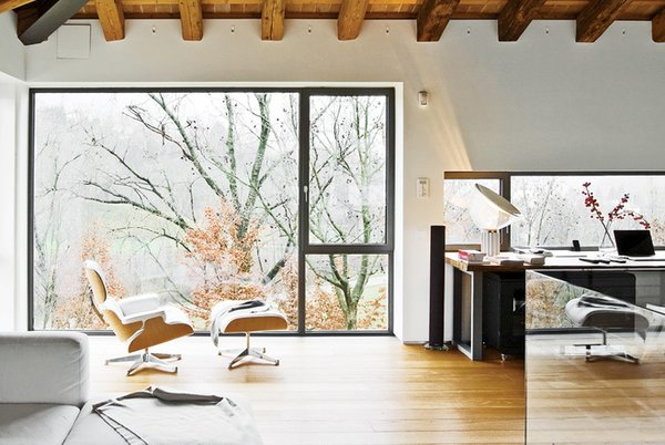 Architect Filippo Caprioglio punched oversized, single-pane windows into the facade of an old farmhouse in Tuscany to open up the interiors to the rolling scenery outside.