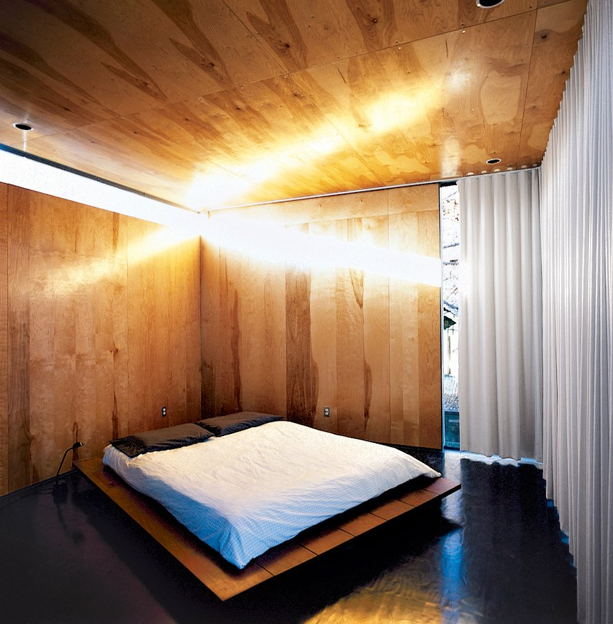 Bedroom, Bed, and Dark Hardwood Floor If you're looking for the ultimate minimalist bed frame, a platform bed with edges that extend beyond the mattress allow it to double as a bedside table, eliminating the need for other furniture.  Photos from Red, Wood, and Blue