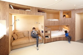 """To free up space, beds, shelves, and a sofa appear to be built into the wall. To accommodate the gentle curve of the """"unit,"""" the architects selected birch plywood. A large window is opposite of the beds."""