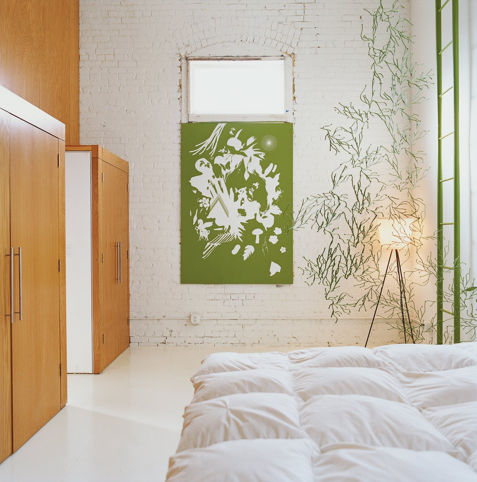 The bedroom is decorated minimally by another Vogt screenprint, and a strand of green Algue.  Modern Bedroom Ideas  by Matthew Keeshin from A Minneapolis Building That Has Lived Multiple Lives Is Revitalized by a Coffeehouse Owner