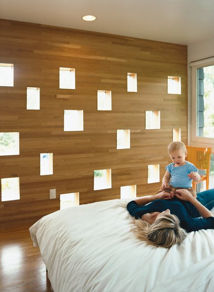 Karie and Mason enjoy a playful loll on the bed in the Deans' new master bedroom. The perforated wall facing the neighbors' backyard offers a great deal of diffuse light while still managing to conceal the Deans' boudoir from prying eyes.