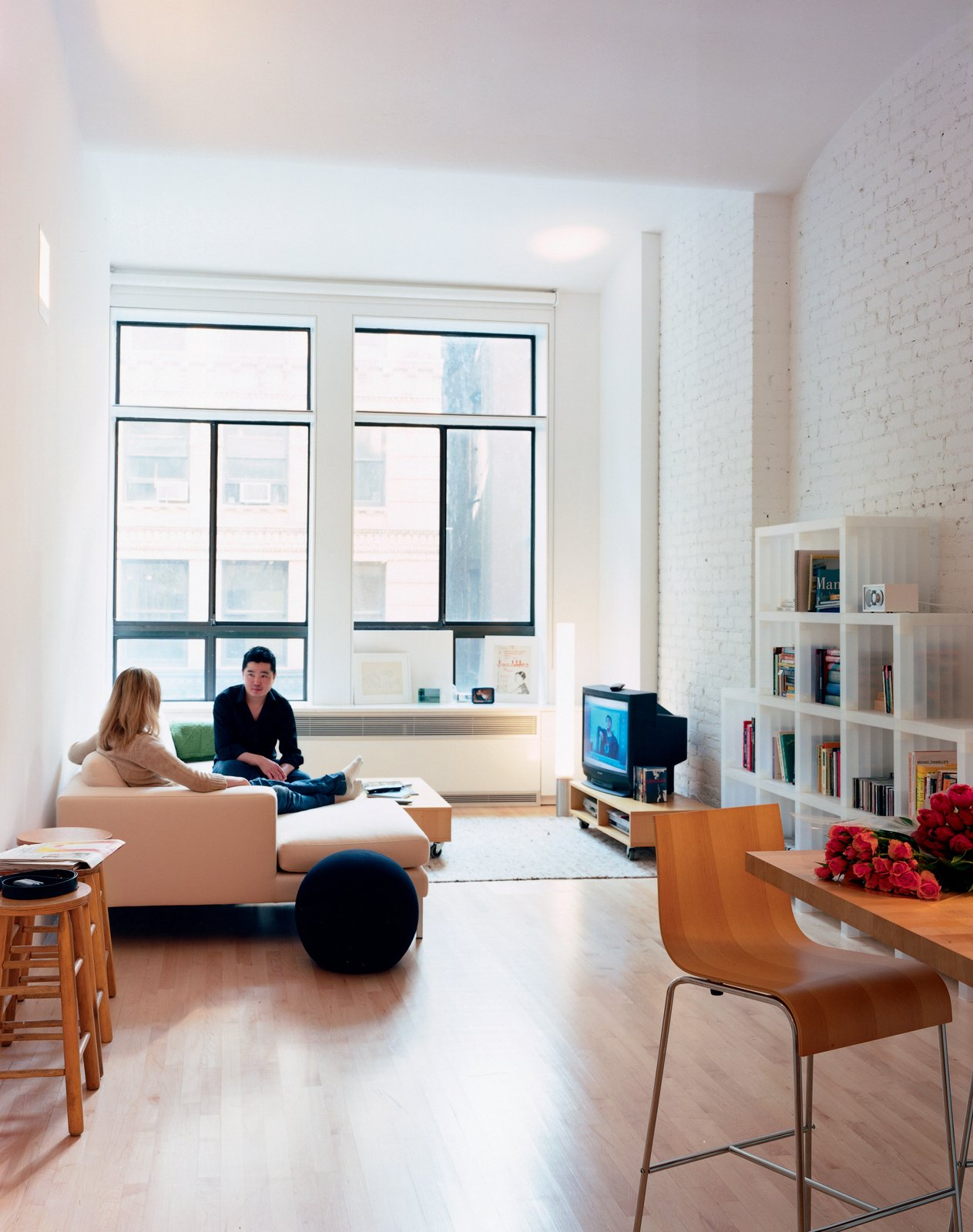 """A reflective light shelf sits atop the lower window units. """"When light hits the shelf, it reflects back on the ceiling,"""" Woo explains. """"This is a very deep space, so we tried to bring the light as far back as possible."""" The Neo sectional chaise by Niels Bendsten provides comfortable seating for Wonbo and his friend Alyssa Litoff. The Cubits shelves are by Doron Lachish.  Photo 4 of 7 in Big City, Little Loft"""