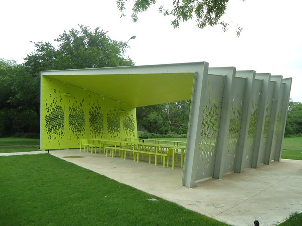 The arresting lime-green interior makes the pavilion at once blend with and stand out from its surroundings. Photo by Architexas.