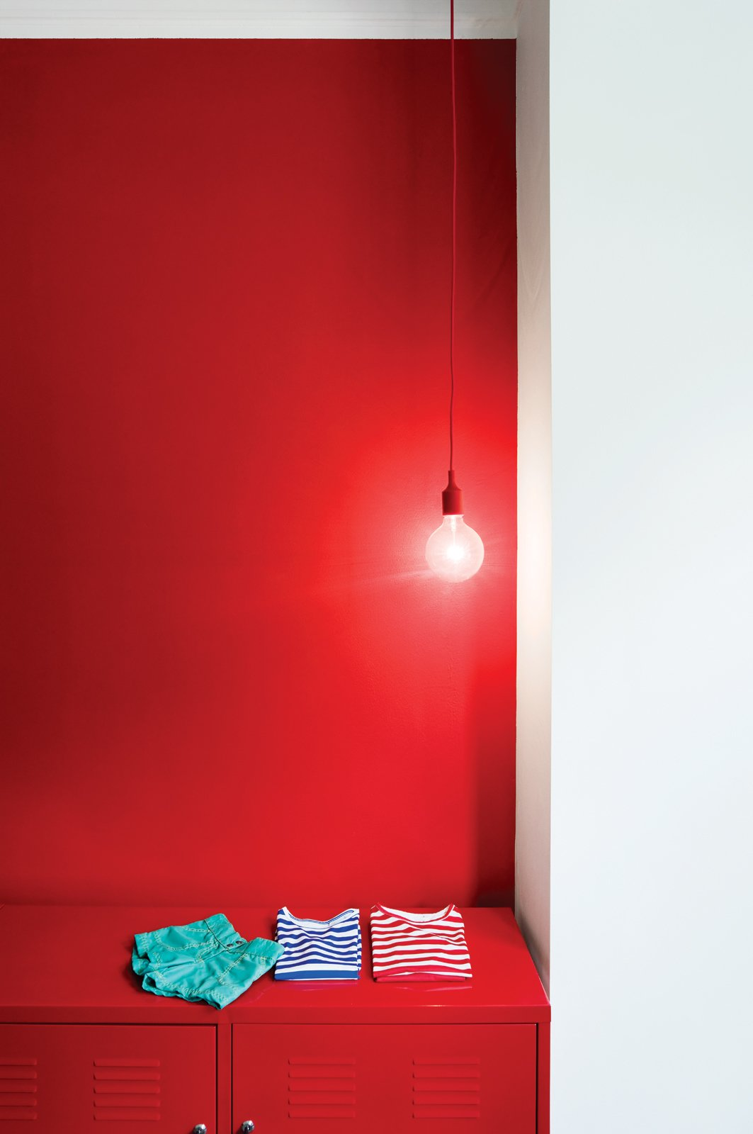 """Storage Room and Cabinet Storage Type Happy Accent  Now that the interior's palette is firmly in place, Winterhalder has slowly been adding splashes of color. E27 pendant lamps from Muuto in the kitchen and guest room have   red cords; one wall in the guest room is also red, with matching red locker storage. The inside of the front door is painted bright green. """"For me, they're kids' colors,"""" she says. """"I just love them.""""   muuto.com  Photo 10 of 21 in Red, Red, and More Red! 20 Bold Interiors That Make a Statement from Paint it Black"""