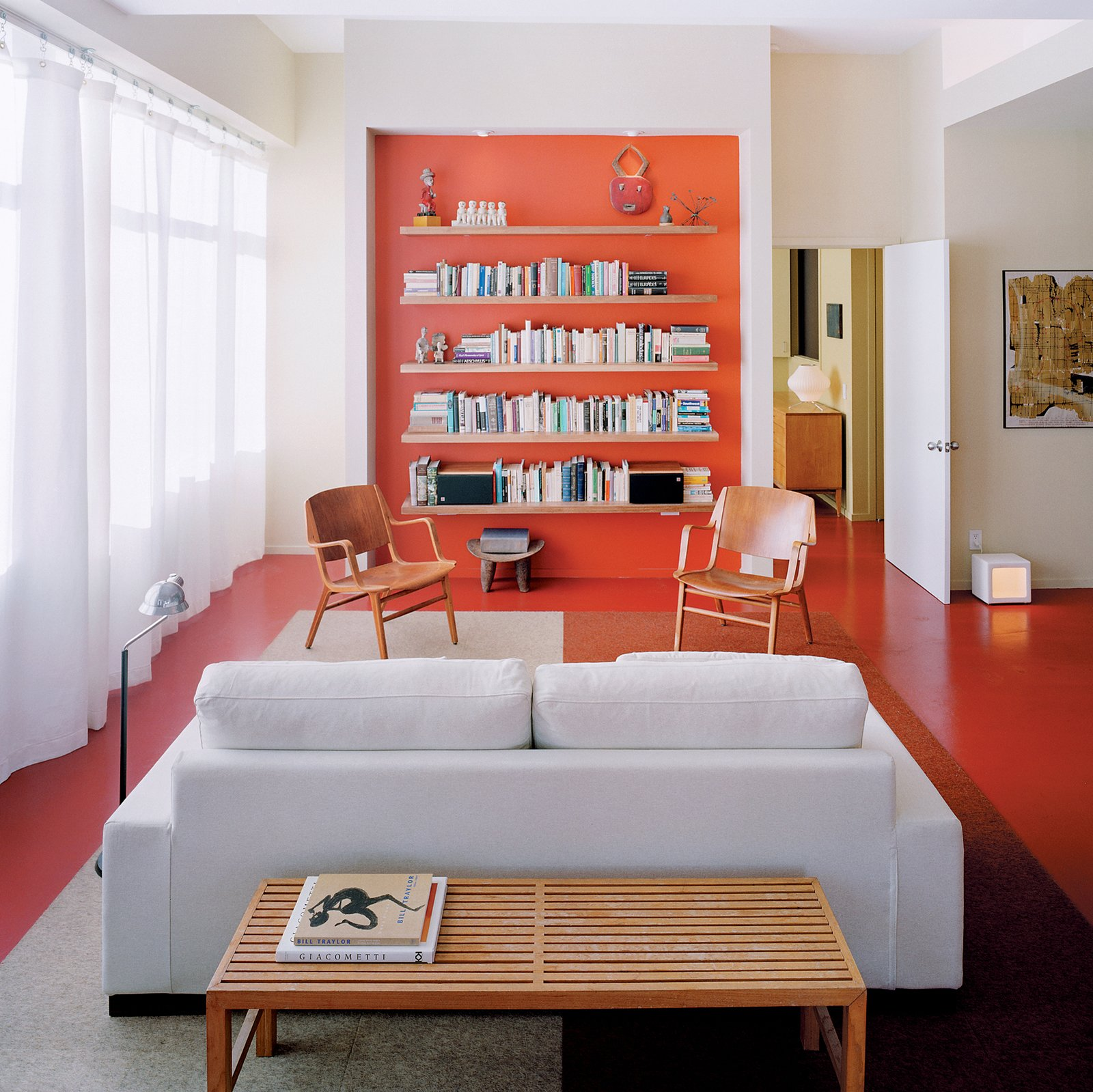 Living Room, Sofa, Chair, and Shelves Architect Grant explains that the recessed orange wall with built-in storage shelving is a counterpoint to the view of Boston in the opposite direction.  Tips for Creating a Comfortable Living Room by Drew McGukin from Urban Usonian