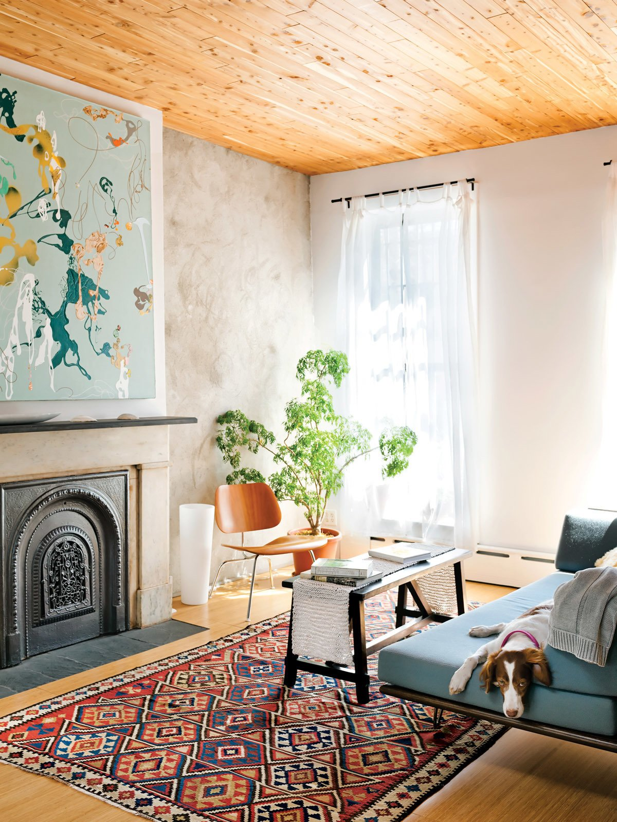 "Living Room, Light Hardwood Floor, Sofa, Standard Layout Fireplace, Chair, and Rug Floor In the living room Daphne the dog keeps company with a Case Study Day Bed from Modernica, a LCM chair by Charles and Ray Eames for Herman Miller, and a painting by the Brooklyn artist Joyce Kim.  Search ""Creative Types"" from New Prospects"