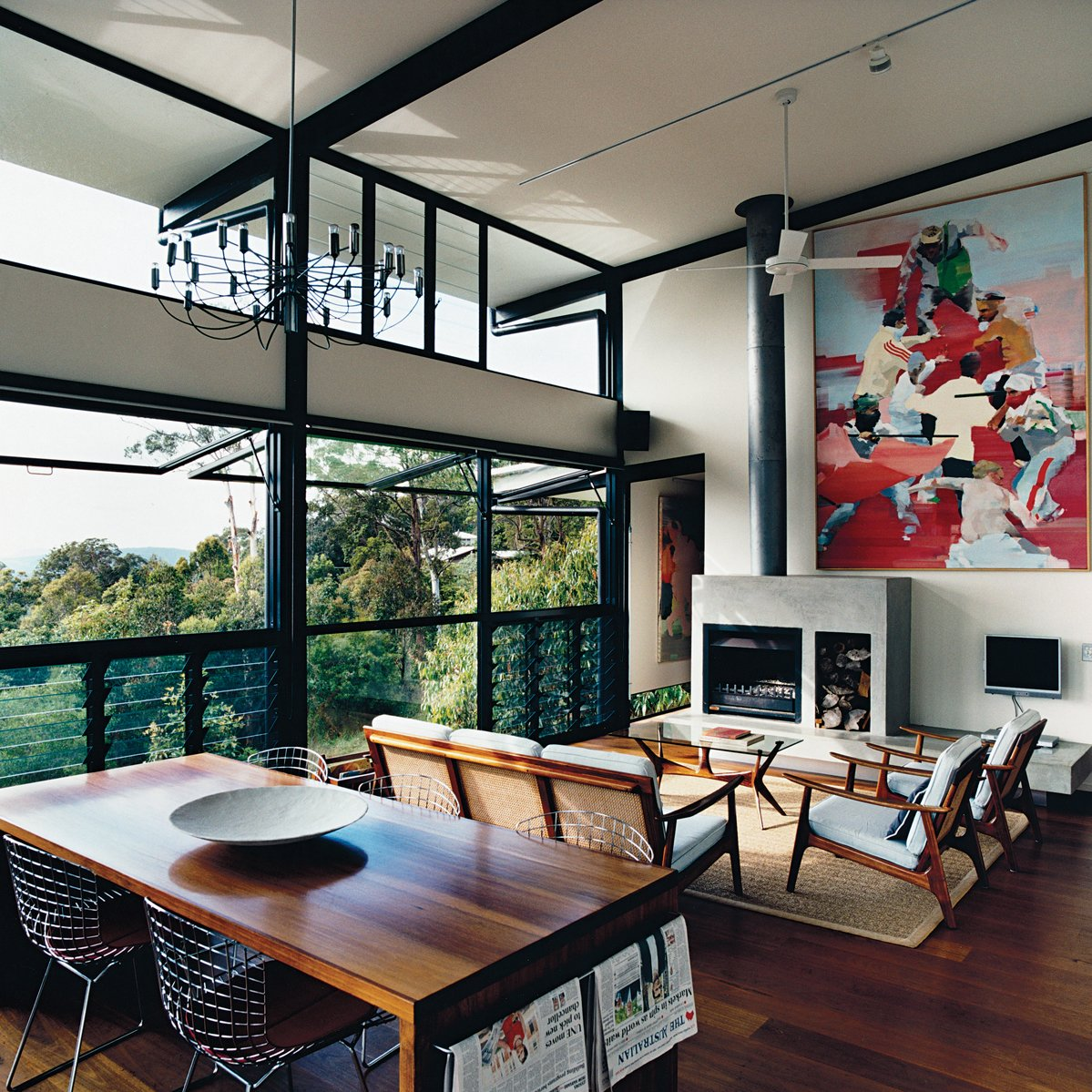 The open-plan living room was inspired by the couple's previous residence, a London loft. The paintings are by Dunlop. The louvered floor-to-ceiling windows, ceiling fan, and sliding deck doors usher in sea breezes and encourage good air circulation. Photo by Richard Powers.  Daring Hillside Homes by Diana Budds