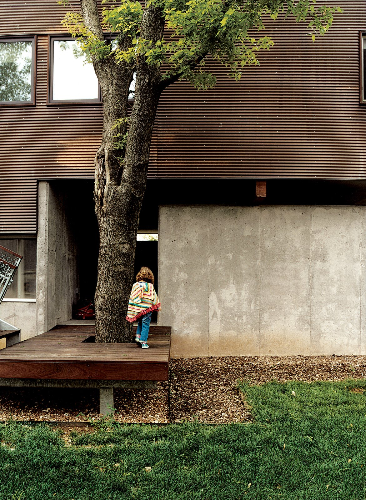 """Outdoor, Grass, Small Patio, Porch, Deck, Wood Patio, Porch, Deck, and Trees Rather than a traditional frame construction, the Kansas City, Missouri, home of architect Jamie Darnell and Michele was built using SIPs (structural insulated panels) that came in four-by-eight-foot sections in kit form. With ladderlike steps leading to the front door, the place feels like an ultrapolished tree house. The arboreal atmosphere was intentional. """"We're tree people,"""" Jamie says. Jamie built the decking, of ipe, to accommodate a tree by the entrance to the garage.  Photo 1 of 9 in Affordable, SIP-Built Family Home in Kansas City"""