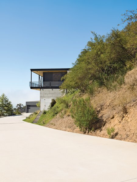 To deal with a Malibu site's sharp incline, architect Bruce Bolander set the steel, concrete, and glass house on caissons. A deep wraparound porch nearly doubles the home's living space and offers the ideal perch for outdoor dining and taking in spectacular views of the surrounding canyon. The garage serves as resident Dave Keffer's home office. Photo by J Bennett Fitts.