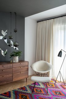 Two classics are bound to work well together. Here, In a corner of this master bedroom, a black Greta Grossman Grasshopper lamp sits next to a white Bertoia Diamond chair with matching ottoman. Photo by Andrew Cammarano.