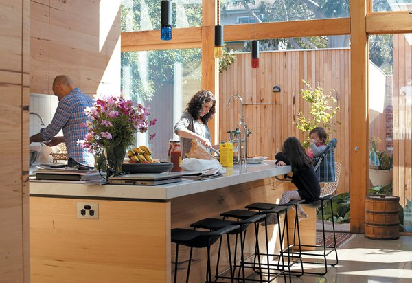 The large, naturally lit kitchen is the heart of the house. Messmate-clad cupboards and huge expanses of glass dominate the space where Angelucci uses the sink, Gorman works at the kitchen island, and Pepa and Hazel look on. Play in the courtyard between the kitchen and garage is easily supervised and enclosed from the alley behind the house.