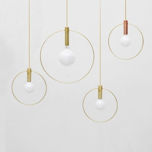 AURA LIGHT  Intending to take light to an elemental place, the Aura Light from Ladies & Gentlemen Studio features two simple, primary elements: the light source—the bulb—and the illumination, which is highlighted by a brass ring. The result is a simple but sophisticated fixture that can be used as a singular suspended piece, or can be grouped with other Aura Lights for a more dramatic, installation-like effect. When the Aura Light is turned off, the minimalist pendant looks delicate and spare; it does not interrupt its environment. When it is illuminated, the aptly named Aura Light produces a lovely, halo-like diffusion of light, enhanced by its metal ring.