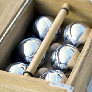 AKIKO PENTAQUE BOCCE GAME SET  A beautifully designed version of the classic lawn game, bocce, the Akiko Petanque set includes a set of six chrome bocce balls and a teak box for storing and carrying the game. The box has a hinged cover with a rectangular cut out, so the teak handle can be used when the box is closed. A collaboration between Danish designer Hans Thyge and Japanese designer Akiko Kuwahata, this set can be used to play, or can be set on a bookcase or table as a distinctive display piece.