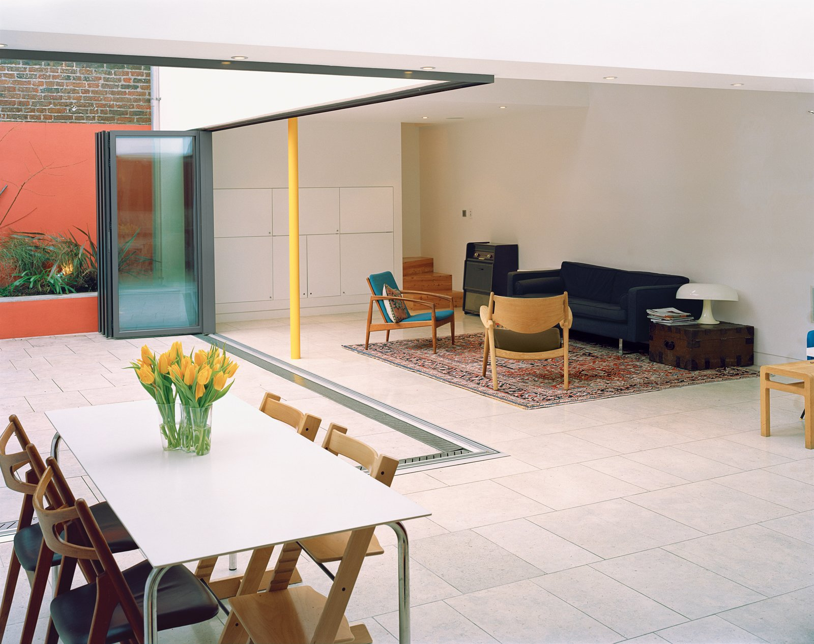 The glass wall separating the main living area and the inner courtyard garden opens like an accordion to create a barrier-free transition. Built-in planters along the walls of the courtyard add greenery without eating into the valuable surface   area of the courtyard.  Brilliant Examples of Indoor-Outdoor Homes by Zachary Edelson from A Slender Geothermal Cottage in London