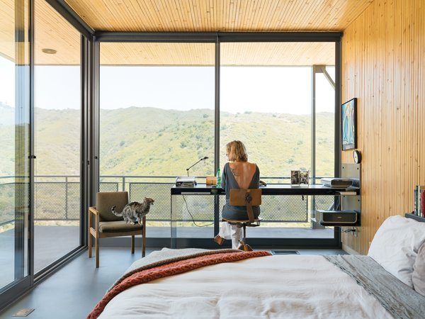 "Architect Bruce Bolander made the most of a limited footprint in a house he designed in a Malibu canyon. With the small bedroom unable to accommodate any ""normal"" size desk, the architect designed a very thin custom steel desk where resident Heidi Wright works. The floor-to-ceiling sliding glass doors from Metal Window Corporation open the entire corner of the room up to the outdoors. ""The mountains across the way are almost like another wall—they contain the space to the point that you feel like you're in a much bigger space, that you're part of the overall landscape,"" says Bolander. Photo by J Bennett Fitts."