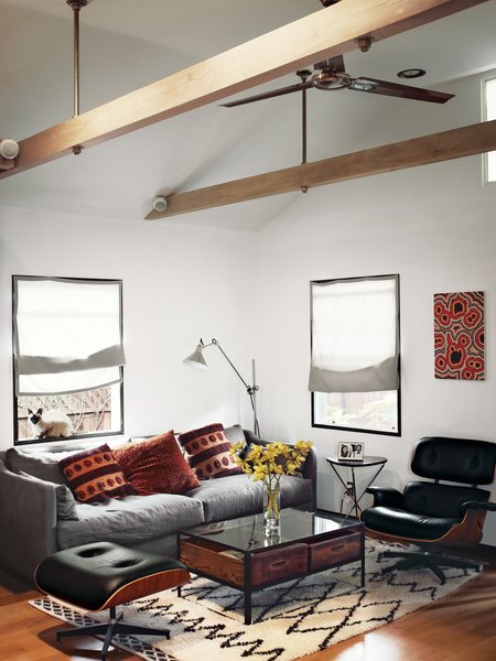 In the living area of actor Vincent Kartheiser's Hollywood cabin, redesigned by Funn Roberts to maximize every last inch of space, an Eames lounge chair and ottoman mix with a couch and coffee table by Cisco Home from HD Buttercup. The table in the main room is from West Elm.