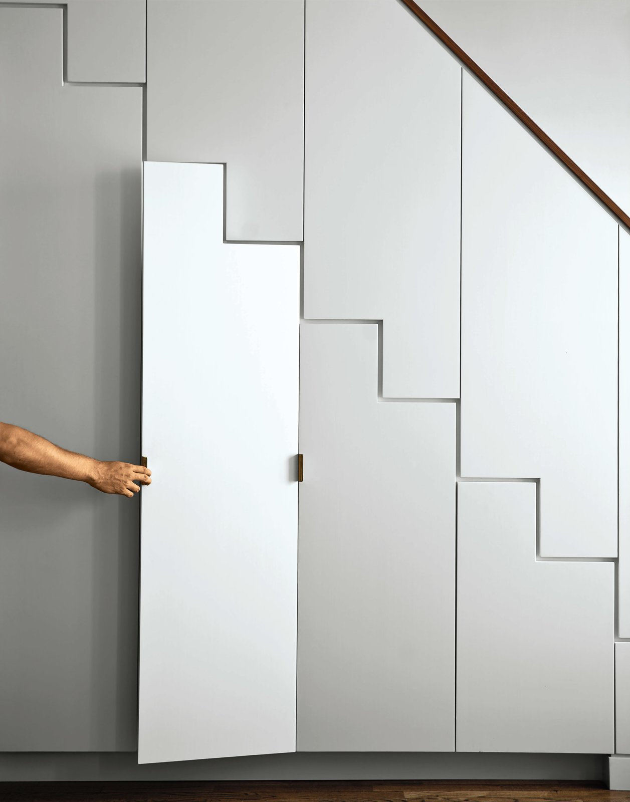 The apartment's main stairwell, disguised as a Shaker cabinet–meets–Japanese tansu stair, houses storage for kitchen ephemera. The finish is hand-painted and accessorized with raw brass hardware.  Storage Solutions: 7 Hidden Closets by Diana Budds from A Minimal Yet Mighty Brooklyn Apartment