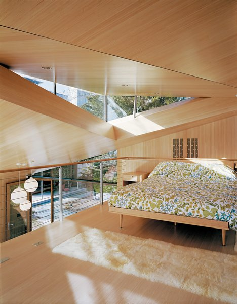 "A lofted sleeping space furnished with a king size Design Within Reach American Modern bed was made possible when the architects raised the ceiling to create a triangular skylight. The move carved out enough headroom to make the second-floor space usable, while still keeping the cottage in compliance with strict local zoning rules for ""accessory"" buildings."
