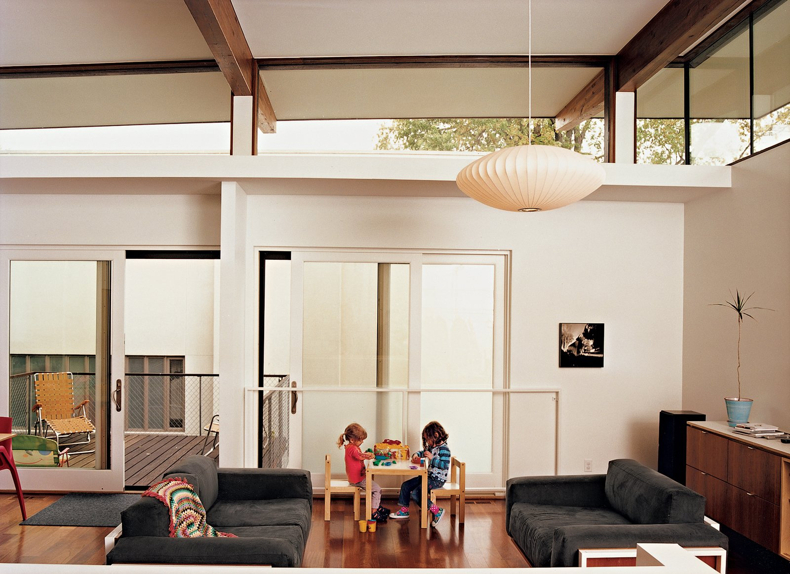 Living Room, Pendant Lighting, and Sofa Judith and Maple at work in the living space, which has a deck off the side and a view of the neighbors' house.  Let It Shine: 7 Elegant Clerestory Windows by William Lamb from Affordable, SIP-Built Family Home in Kansas City