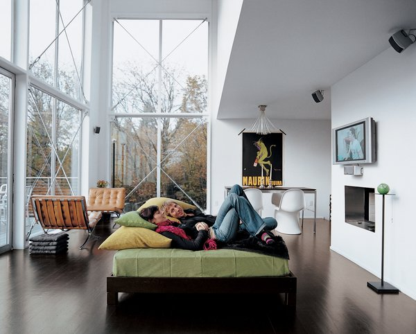 The couple lounges in their great room. The 16-foot-high windows are from Milgard.