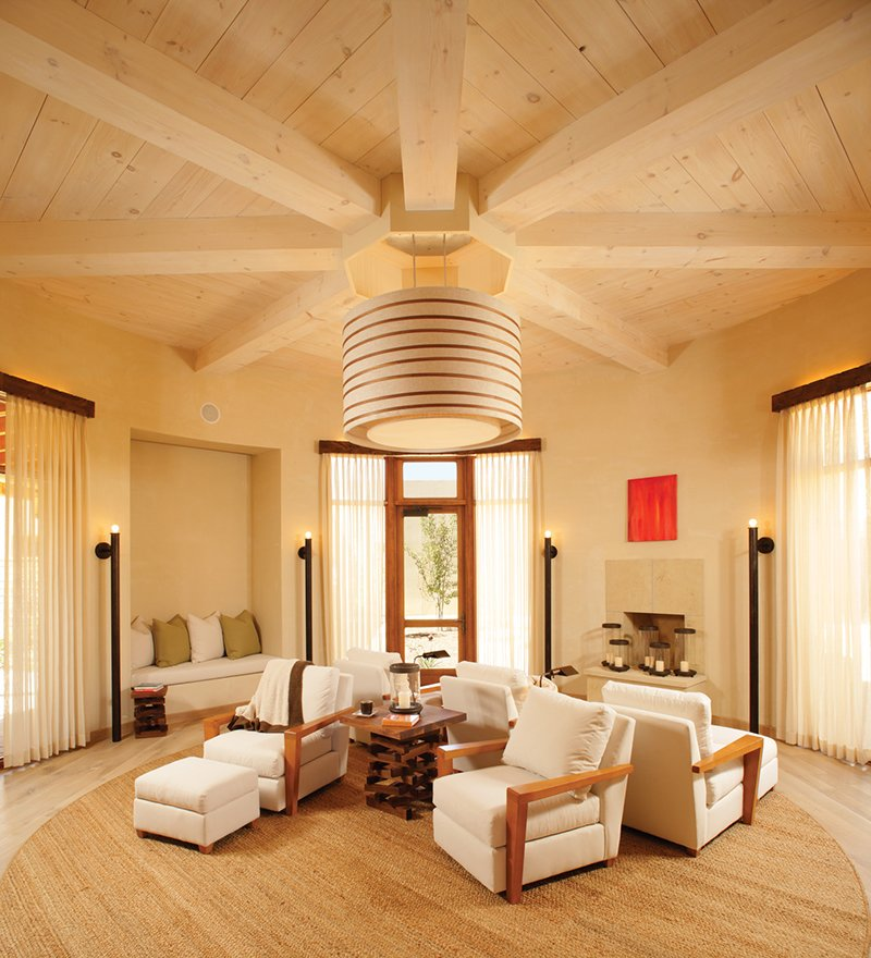 "Designed to reflect sacred Pueblo Indian kivas but with an updated spin, the light and airy round-roomed spa ""warming space"" features a custom walnut-striped chandelier and stacked wood Falo tables—a nod to Native American and New Mexico traditions.  Modern Designs Featuring Exposed Beams by Megan Hamaker"