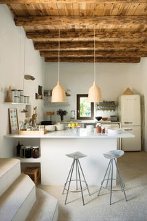 RUG DESIGNER NANI MARQUINA'S SERENE HOME IN IBIZA  Jamaica barstools by Pepe Cortès for Knoll and two Ikea pendants pair nicely with the plaster walls, restored wooden beam ceilings, and polished cement floors in the kitchen. Photo by Albert Font.