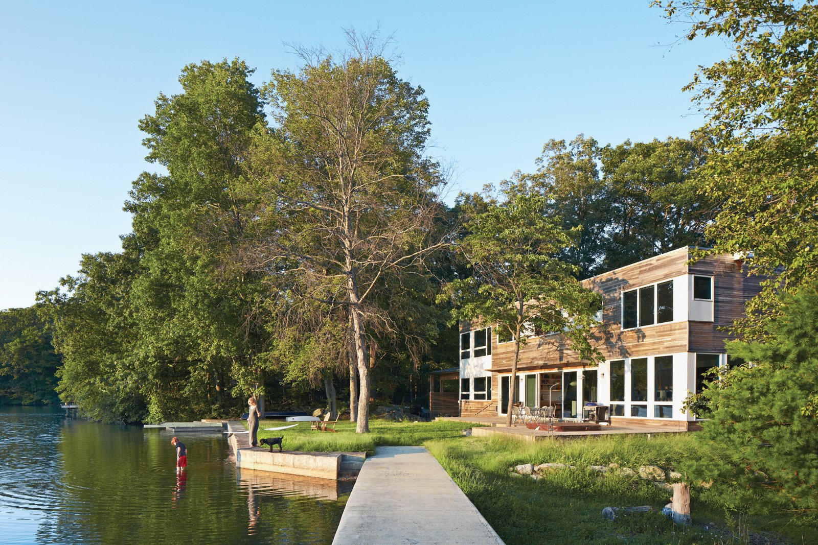 """Exterior, House Building Type, Boathouse Building Type, and Wood Siding Material """"The house's narrow footprint works for us in terms of maximum exposure to the lake,"""" says Gibbs (shown here with son Blake and dog Max on the shore of Lake Iosco). Glass walls and doors by Andersen also mean that Gibbs can keep a close eye on Blake when he's playing in the yard. A plinth of reused bedrock found on the property has become an unintended place for active play.  Best Photos from The New Zealand Native Who Can't Get Enough of the Garden State"""