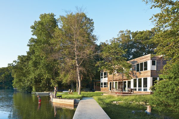 """""""The house's narrow footprint works for us in terms of maximum exposure to the lake,"""" says Gibbs (shown here with son Blake and dog Max on the shore of Lake Iosco). Glass walls and doors by Andersen also mean that Gibbs can keep a close eye on Blake when he's playing in the yard. A plinth of reused bedrock found on the property has become an unintended place for active play."""