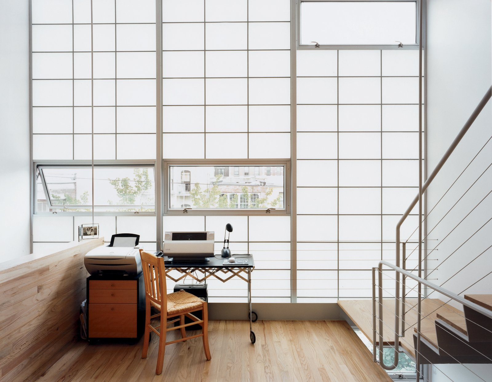 Windows, Awning Window Type, and Metal Clear glass panes set strategically into the otherwise translucent curtain wall expose the mezzanine to fresh air and rear views.  Modern Mezzanines by William Lamb from Harlem Renaissance