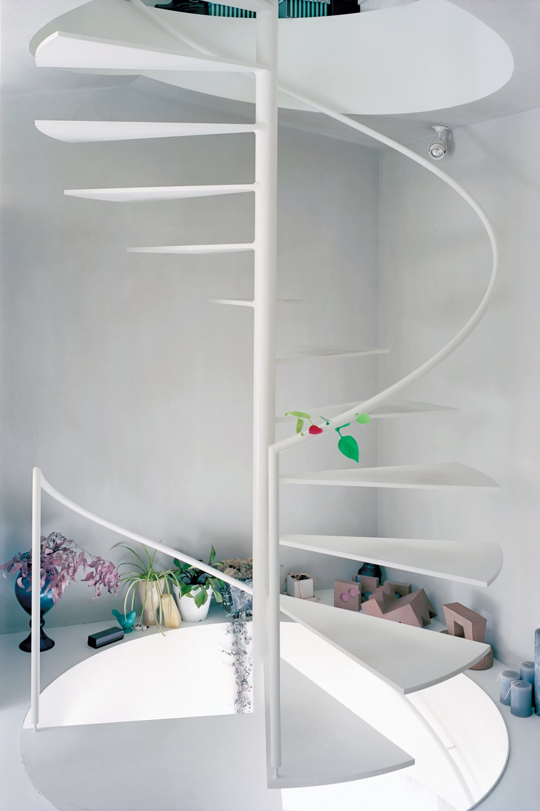 Staircase, Metal Tread, and Wood Railing A steel spiral staircase efficiently links all three floors. With no interior doors, Yurika can keep an ear on the shop from upstairs while maintaining the privacy of her home with the help of the vertical distance.  INSPIRATION * WHITE