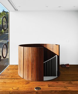 The trip from garage to first floor is through a wood-clad spiral staircase that resembles a giant slatted barrel.