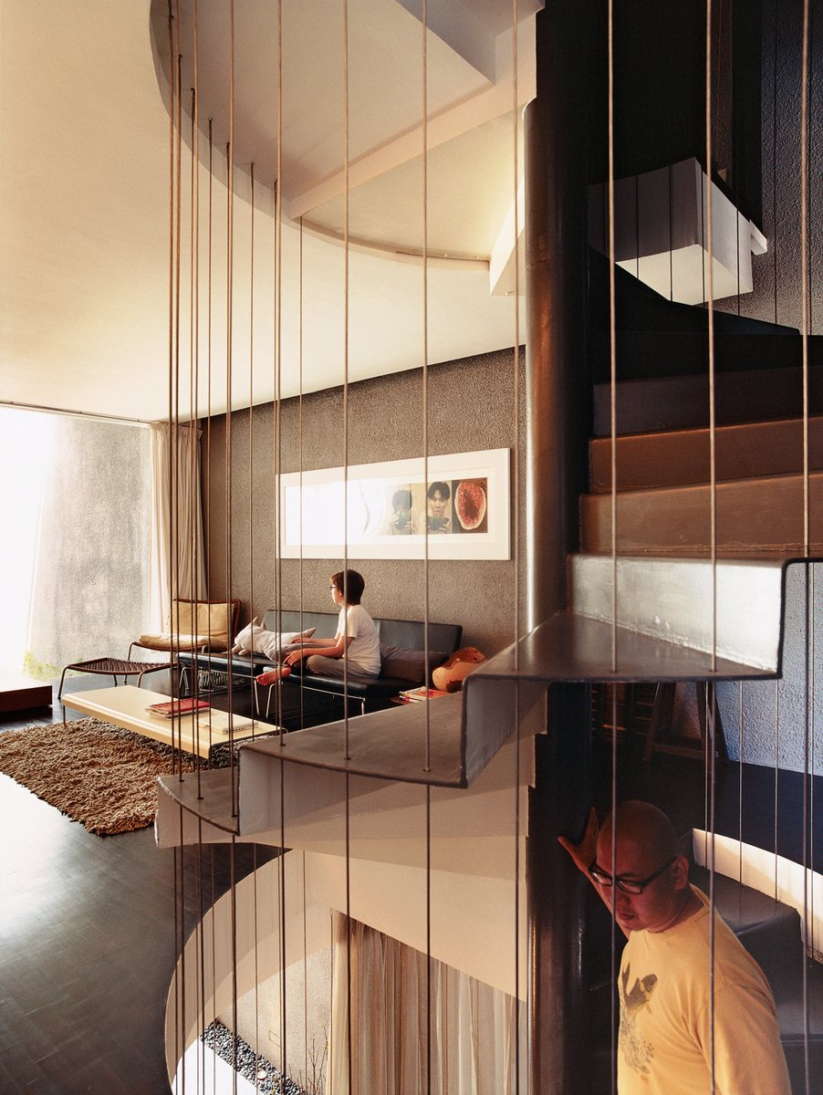 Behind an unassuming 19th-century facade in Singapore, Ching Ian and Yang Yeo live in a very atypical renovation of a typical shophouse. Here, Yeo descends the spiral staircase that connects the public and private spaces while Ian relaxes on a pair of Cappellini Superlight 750 sofas designed by Barber Osgerby. Photo by: Richard Powers  190+ Best Modern Staircase Ideas