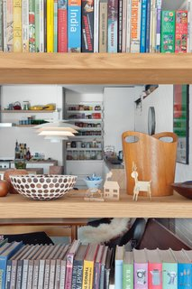 Open shelving between the living room and dining area maximizes light and air flow and showcases eclectic objects, which include old printing blocks found at a garage sale and bowls Tyler's mother bought in South Africa.