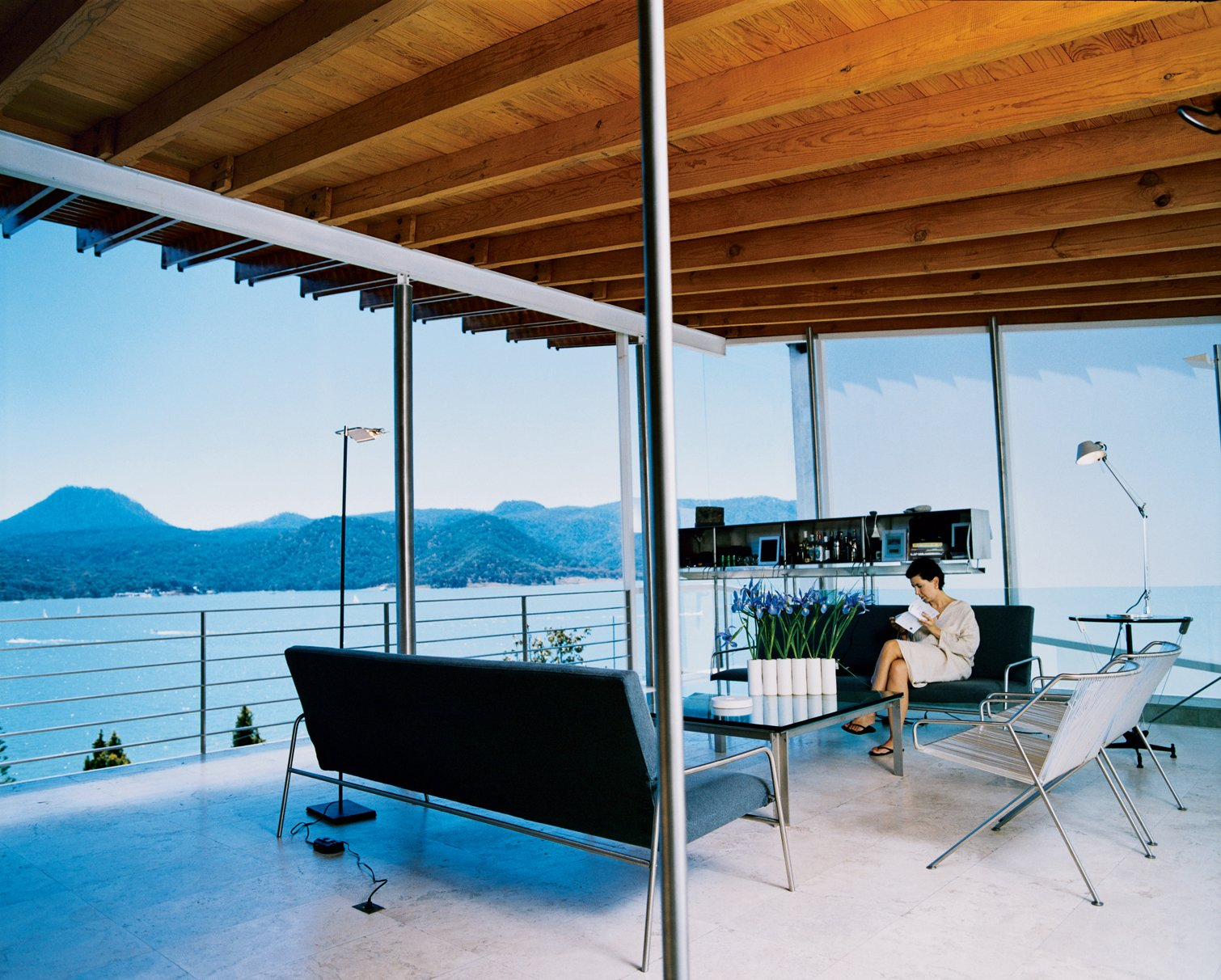 Loredana Dall' Amico reads in the living room, where all the seating was designed by her husband. The floating stainless steel unit behind her is also his design and contains a state-of-the-art stereo system.  Modern Stereo Setups by William Lamb from Reflections on a Lake