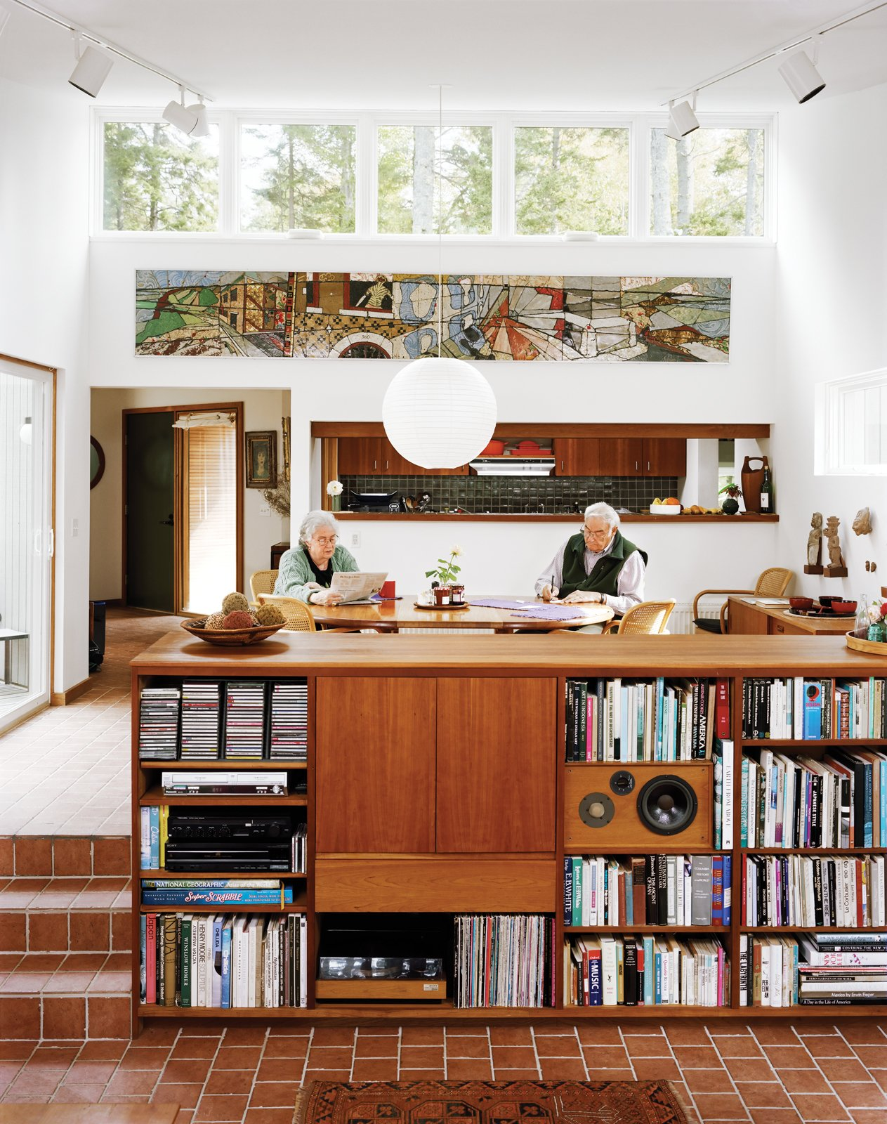Living Room, Shelves, Pendant Lighting, Storage, and Ceramic Tile Floor Cohen and his wife, Sally, sit in the dining room, which along with the connected living room, is a focal point of the house, lighted in part by high, remote-controlled clerestory windows.  Photo 1 of 15 in The Right Track