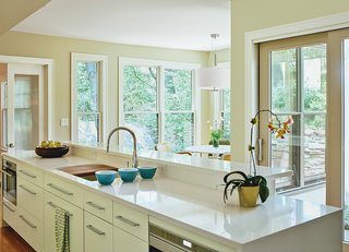 The cabinets are by Kountry Kraft. The Indio sink by Kohler has a built-in walnut cutting board, and the faucet is by Gessi.