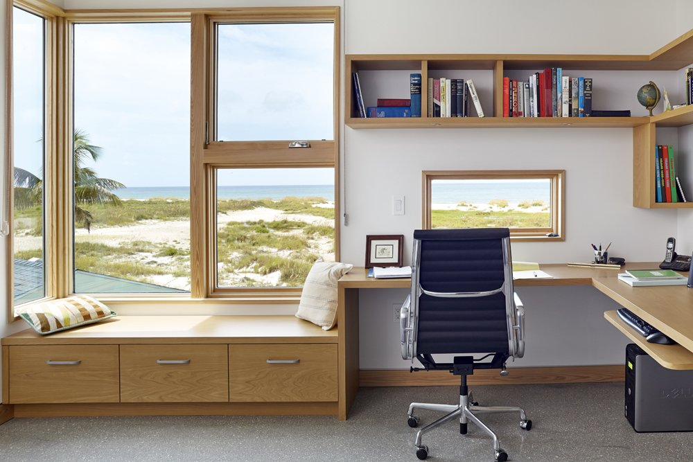 """The guest room doubles as a home office. Here, too, are cypress built-ins framing glass panels that look out onto the sea. The architects call them """"St. Jerome boxes,"""" which is inspired by the classic image of St. Jerome at his desk, lost in thought, with the landscape framed in a picture window beside him.  Photo 8 of 10 in Angular Modern Beach House in Florida"""