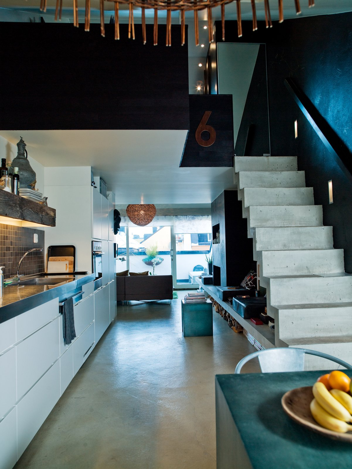 Back downstairs, the kitchen occupies a long wall. The stainless steel worktop was so long—more than 16 feet—that it had to be lifted in through the window. Photo by Per Magnus Persson.  190+ Best Modern Staircase Ideas from Top 10 Houses on Dwell This Week December 19, 2013