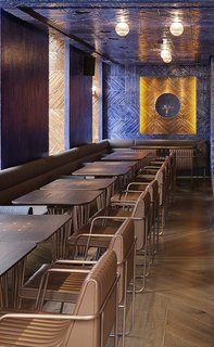 Custom oak, metal, and leather furniture is inlaid with brass detailing.