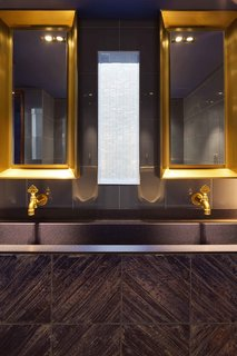 The bathroom features warm metal fixtures.