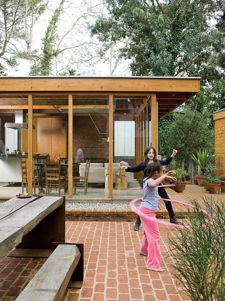 The courtyard acts like an outdoor living room, where the Arnolds' daughter, Josie, plays freely, safe from nearby traffic. The family dines here most of the year at the custom-designed wood-and-steel table. The picnic table set reappropriates the century-old eucalyptus tree that once grew on the site.