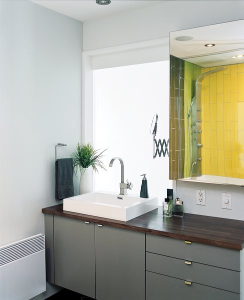 Tiles from Ramacieri-Soligo brighten the bathroom, off the hall. But when it comes to modern bathroom vanities, gray, as seen here, is a popular choice.